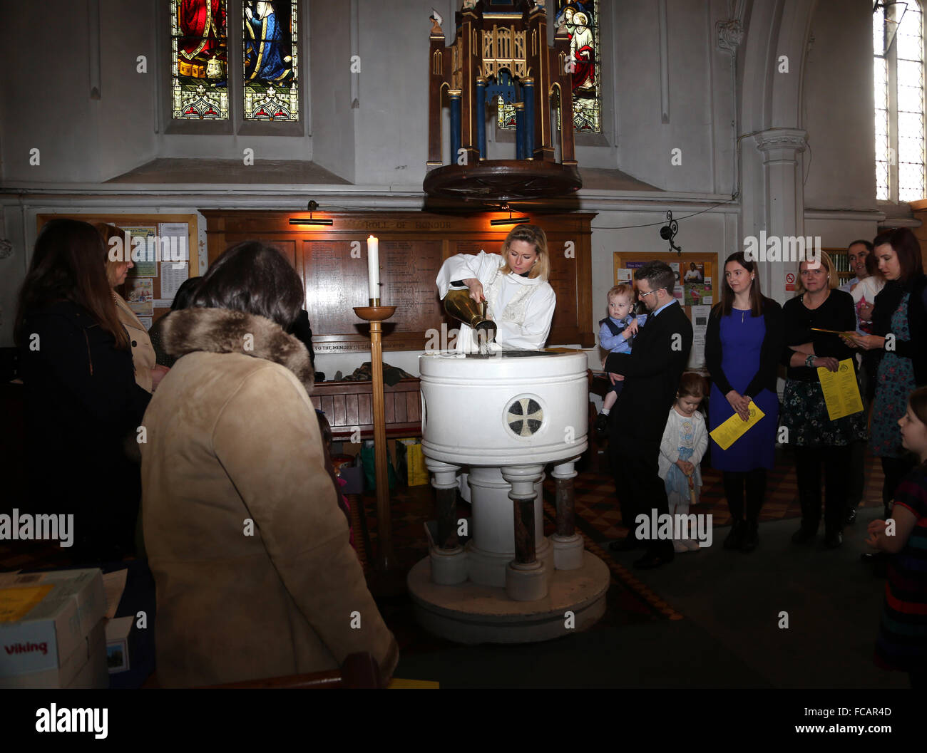 Christening At St Mary's Church Caterham On The Hill Surrey England Female Priest Puring Holy Water In To Font - Stock Image