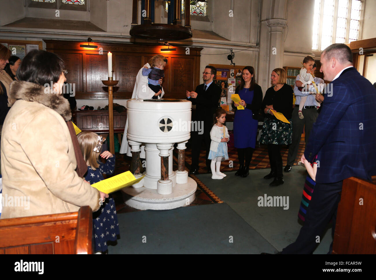 Christening At St Mary's Church Caterham On The Hill Surrey England Female Priest Holding Baby Boy By Font - Stock Image
