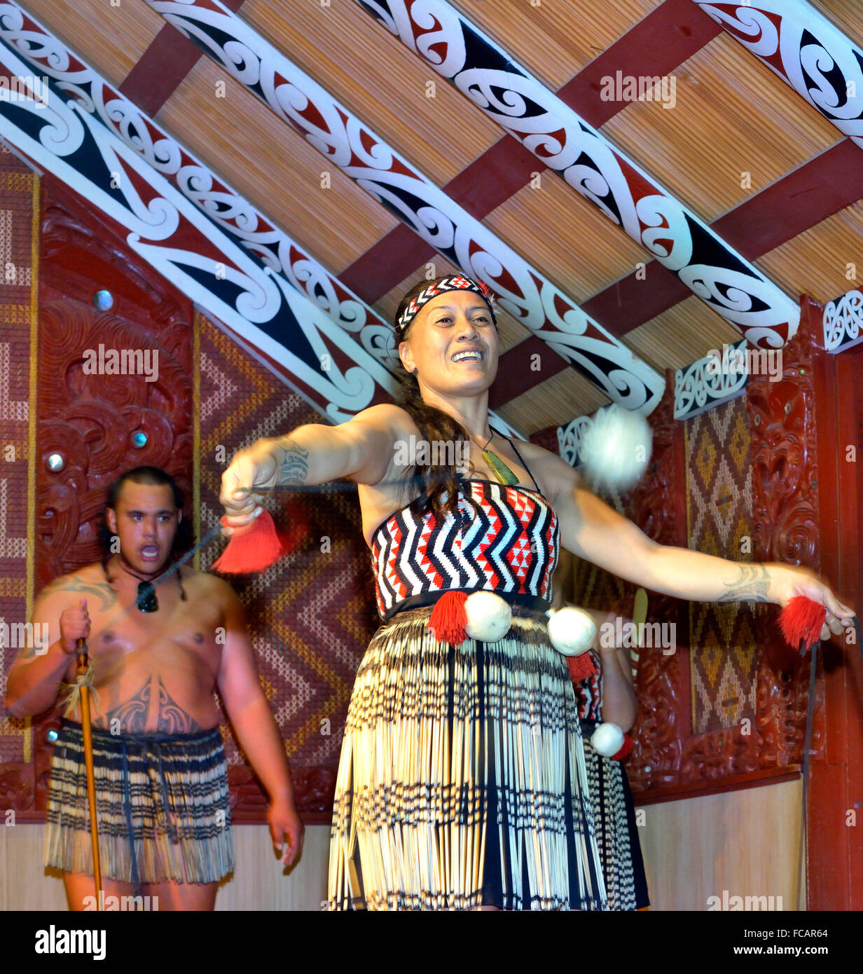 Maori woman and Maori man in Te Puia central Rotorua. Woman is dancing with Poi(s)while the man chants -in the meeting - Stock Image