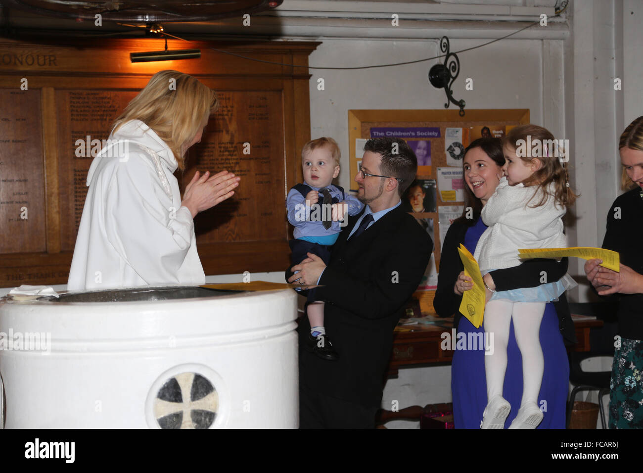 Christening At St Mary's Church Caterham On The Hill Surrey England Female Priest Standing By Font Clapping - Stock Image