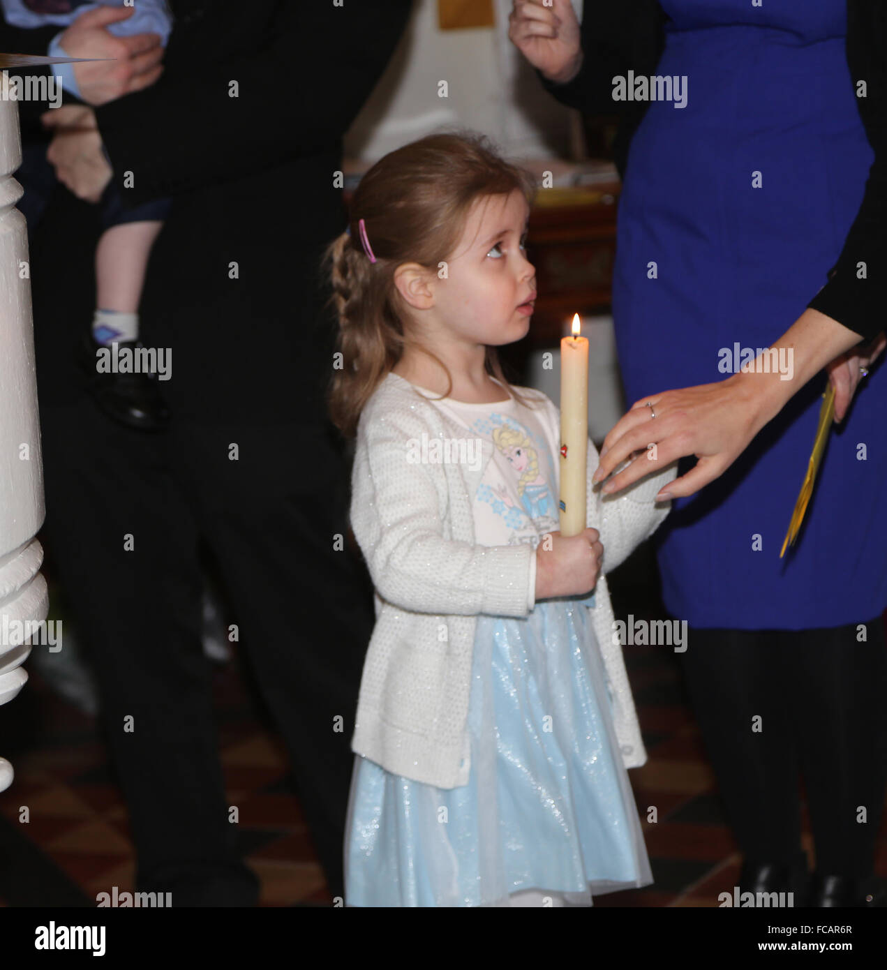 Christening At St Mary's Church Caterham On The Hill Surrey England Girl Holding Baptism Candle - Stock Image