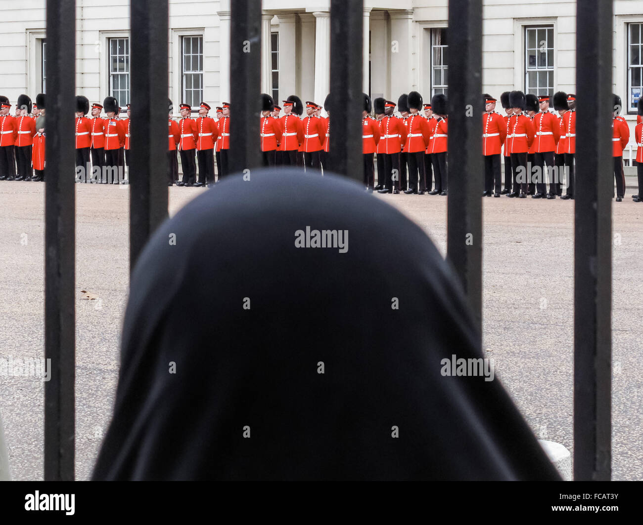 London, UK. 21st January, 2016. A veiled Muslim women watches Queen's guards in Wellington Barracks. Credit: - Stock Image
