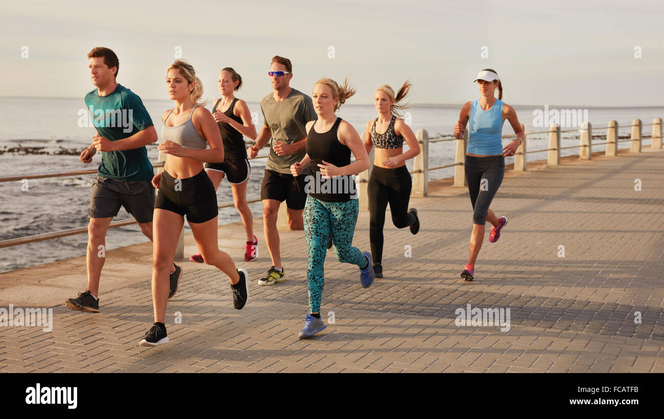 Portrait of young people running along the beach boardwalk by the ocean. Fit young men and women running training - Stock Image
