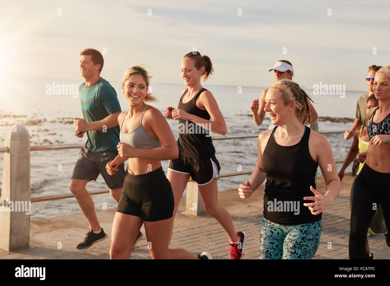 Portrait of healthy young men and women running together on seaside promenade. Active running club group training - Stock Image