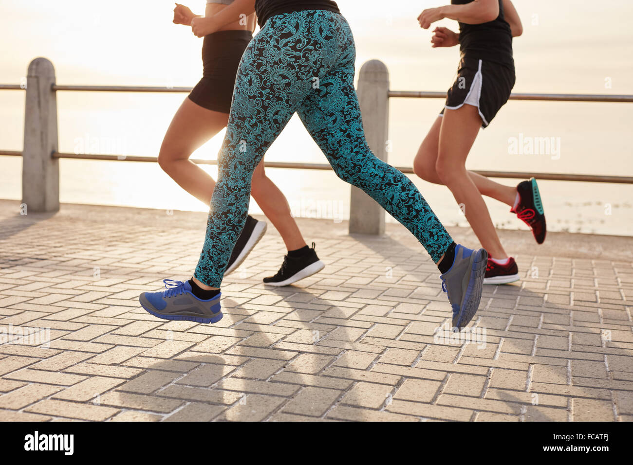 Cropped image of young people running along the sea. Fitness group doing running workout together outdoors. - Stock Image