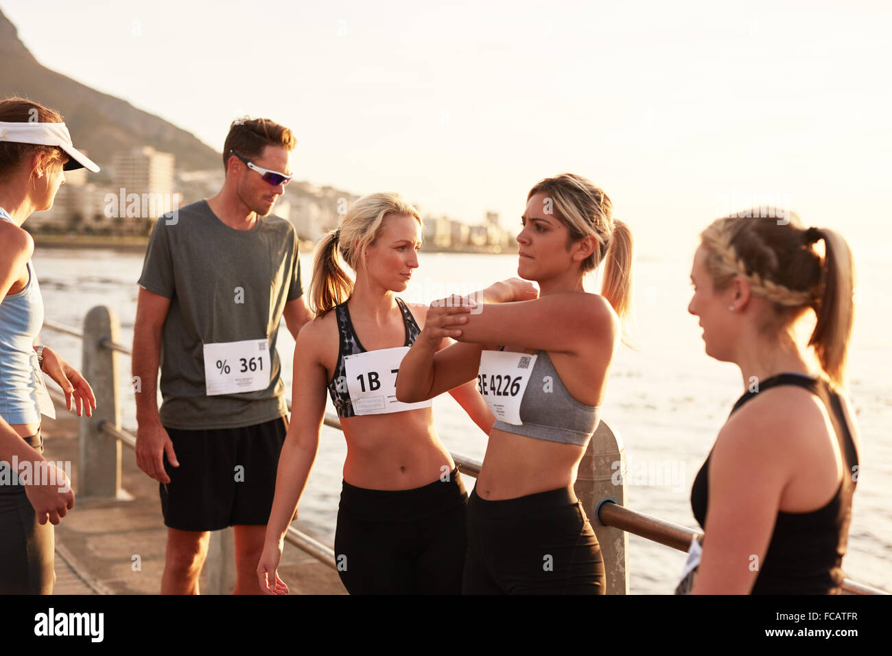 Runners relaxing after finishing the race. Marathon race runners taking a break after a run. - Stock Image