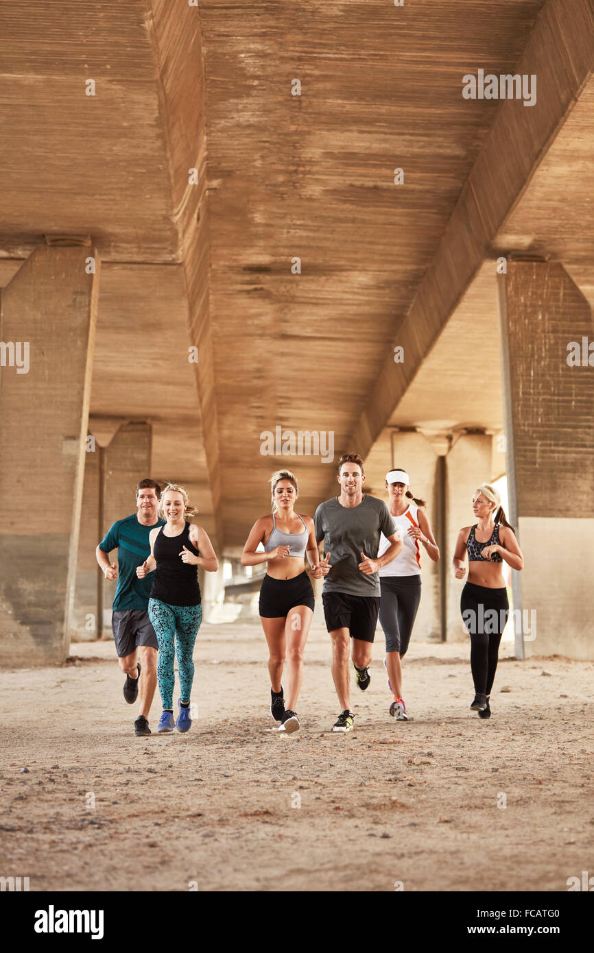 Portrait of healthy young people running under a bridge. Running club group wearing sport clothing training in the - Stock Image
