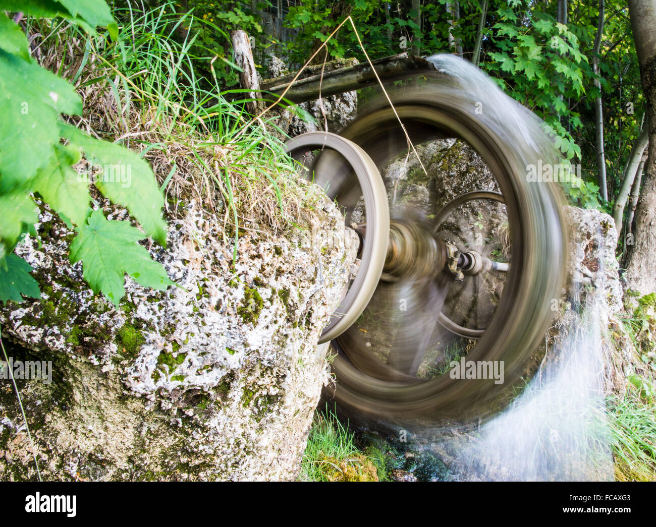 Blurred motion of a vintage spinning water wheel - Stock Image