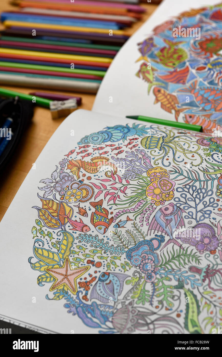 Adult coloring book on table with color pencils - Stock Image