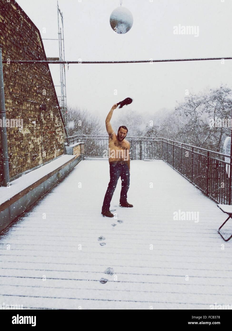 Full Length Of Shirtless Man Throwing Shirt In Snow - Stock Image