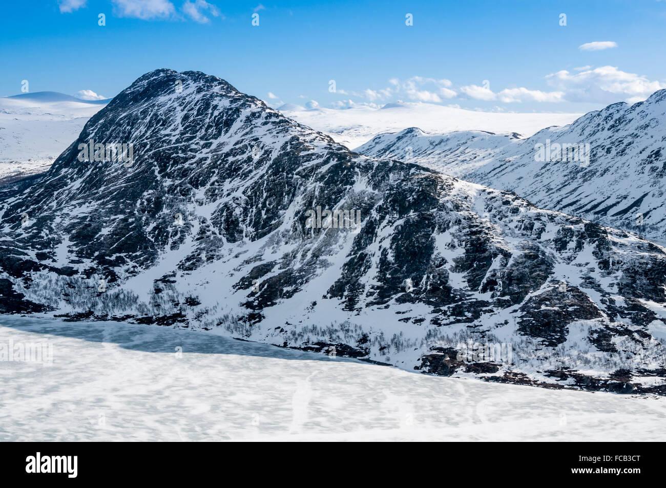 View from ridge Besseggen, narrowest point of the ridge  ('Bandet'),at frozen lake Bessvatn, 400 m below - Stock Image
