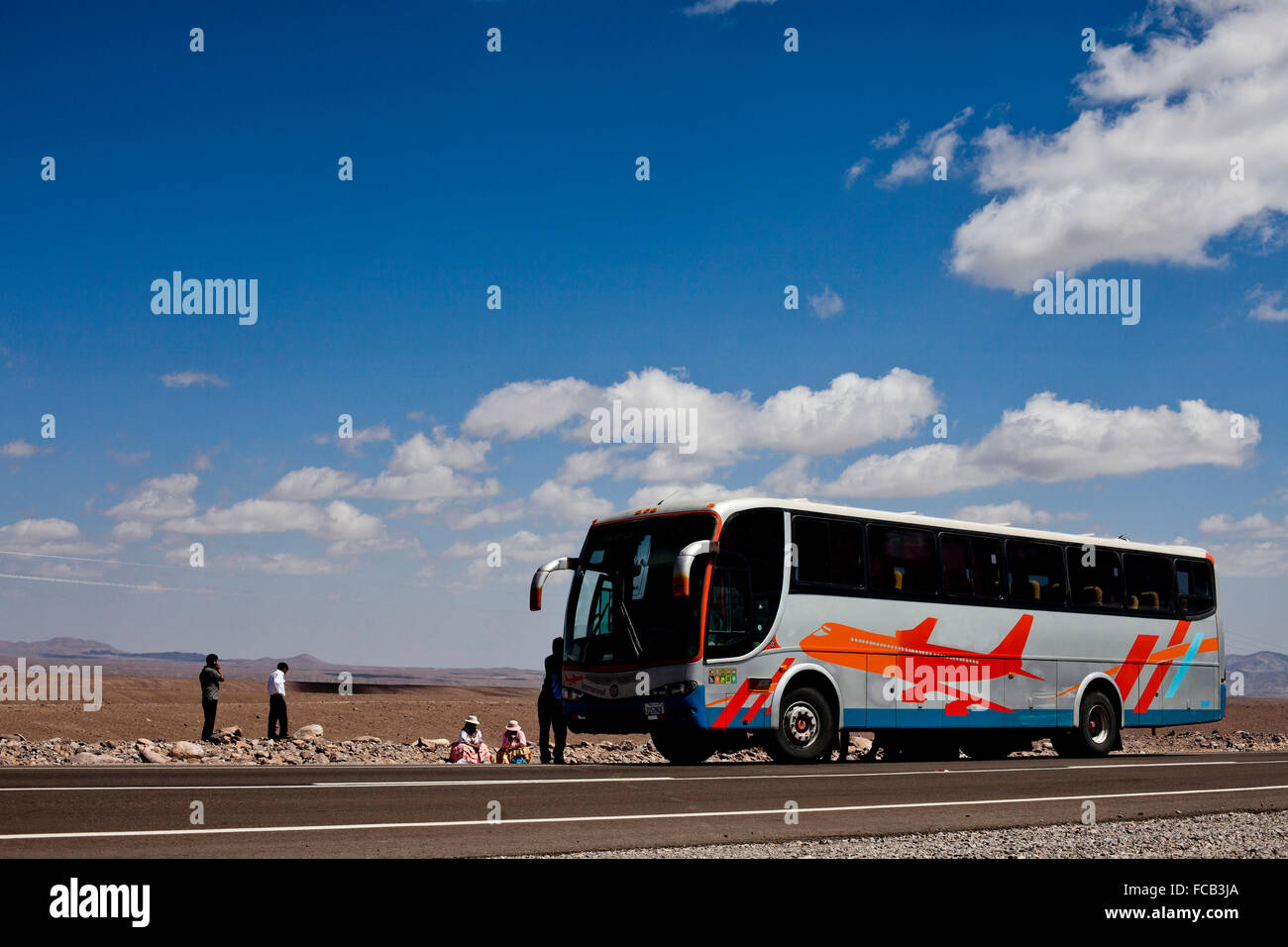 A passenger bus picks up two individuals on the side of the road in the Atacama Desert in Bolivia. - Stock Image