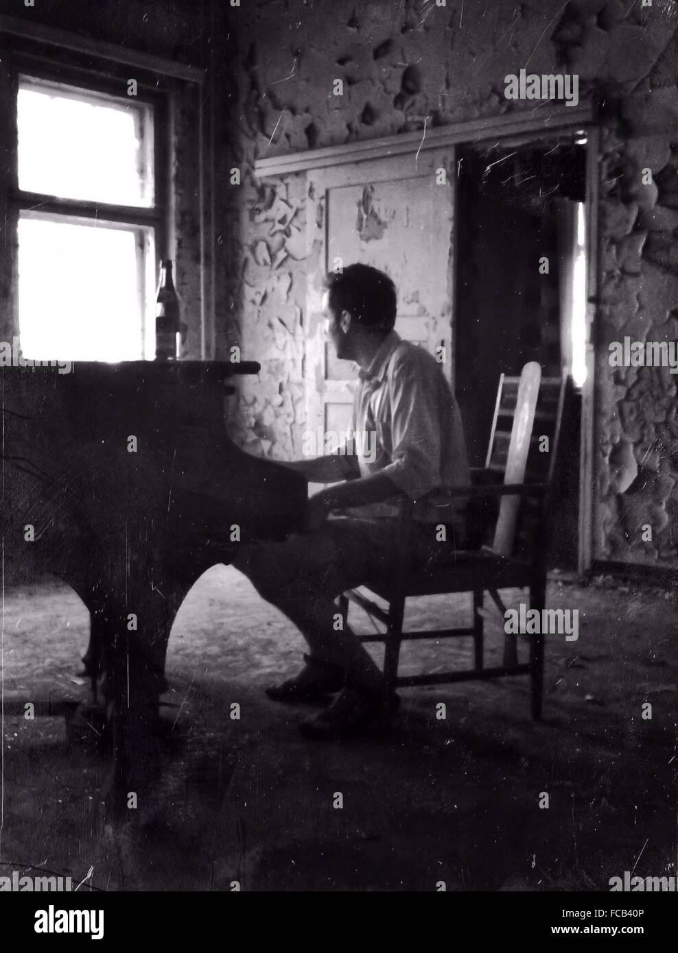 Full Length Of Pianist Playing Piano In Abandoned Home - Stock Image