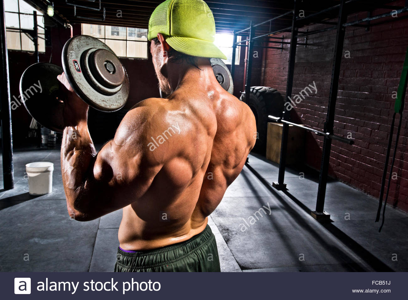 An athlete performs dumbell curls. - Stock Image