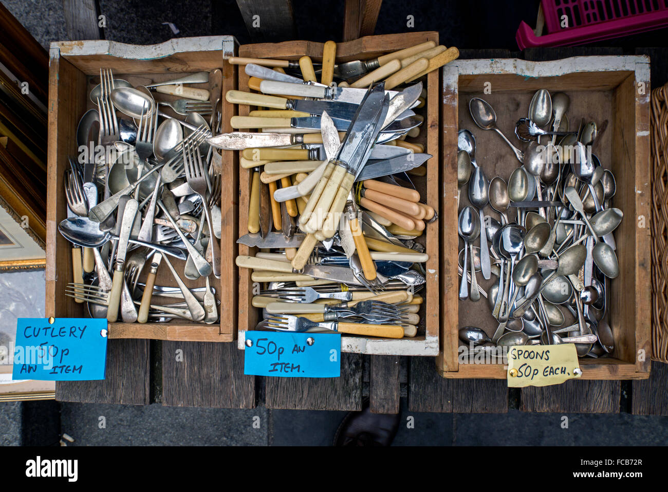 Boxes of cheap, secondhand cutlery for sale on a market stall in Edinburgh's Grassmarket. - Stock Image