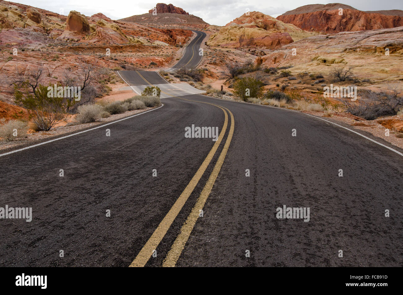 An empty desert road twists and curves through the Valley of Fire State Park. - Stock Image
