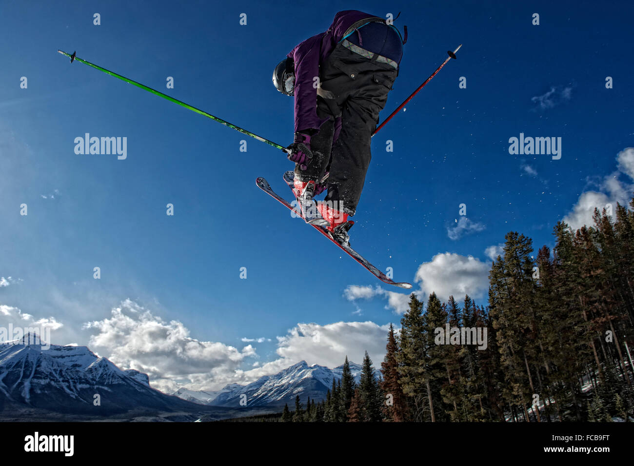 A skier flies high above the ski run at Lake Louise Ski Resort, Canada - Stock Image