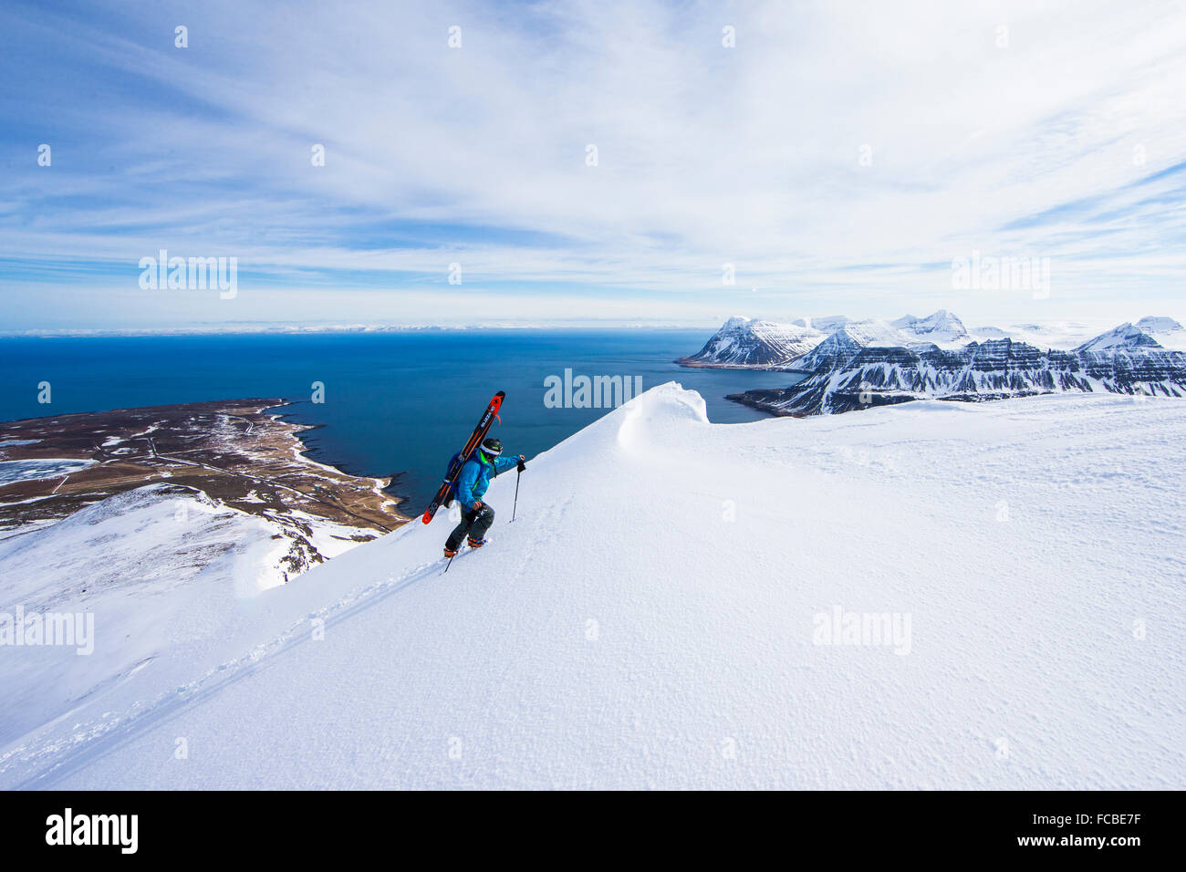A man looks out to the ocean as he reaches the top a a peak. - Stock Image
