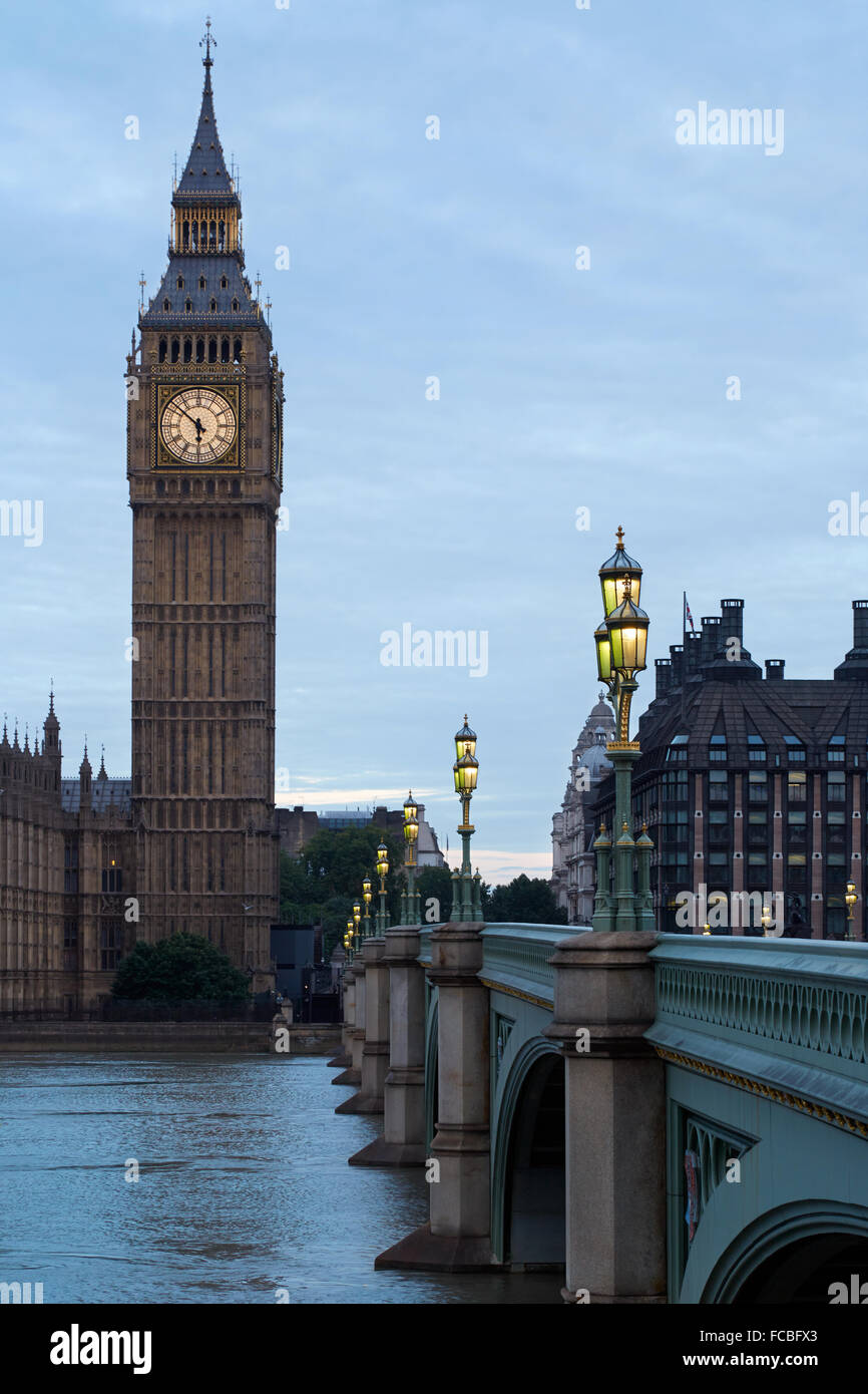 Big Ben and illuminated bridge in the early morning in London, natural colors and lights - Stock Image