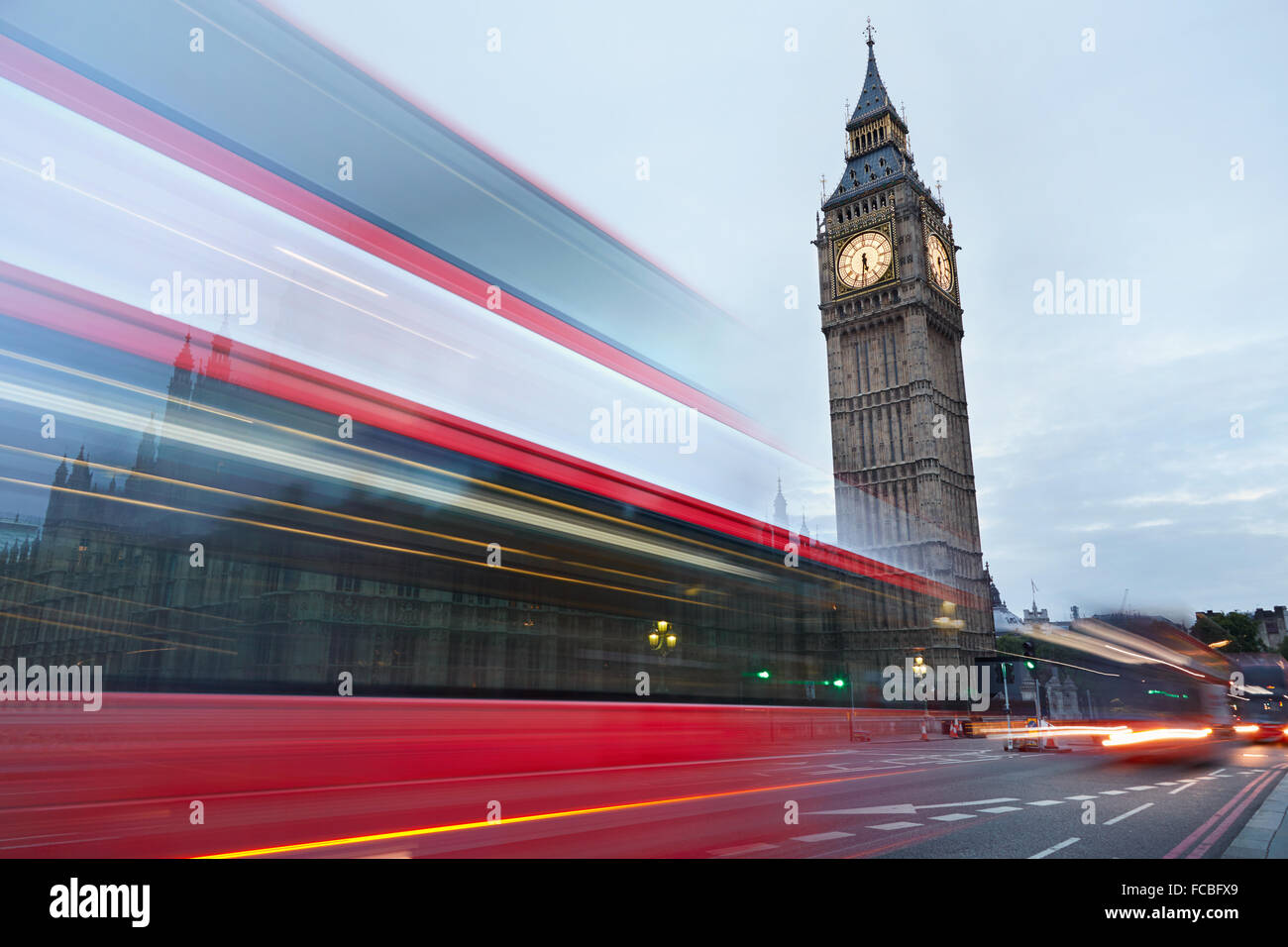 Big Ben in the early morning and red bus passing in London, natural colors - Stock Image