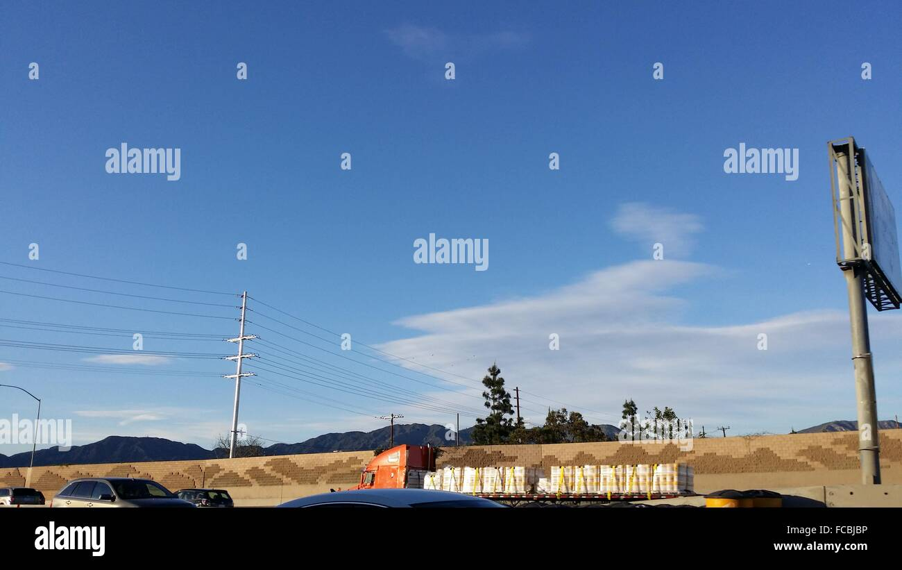 Truck Carrying Freight Against Blue Sky - Stock Image