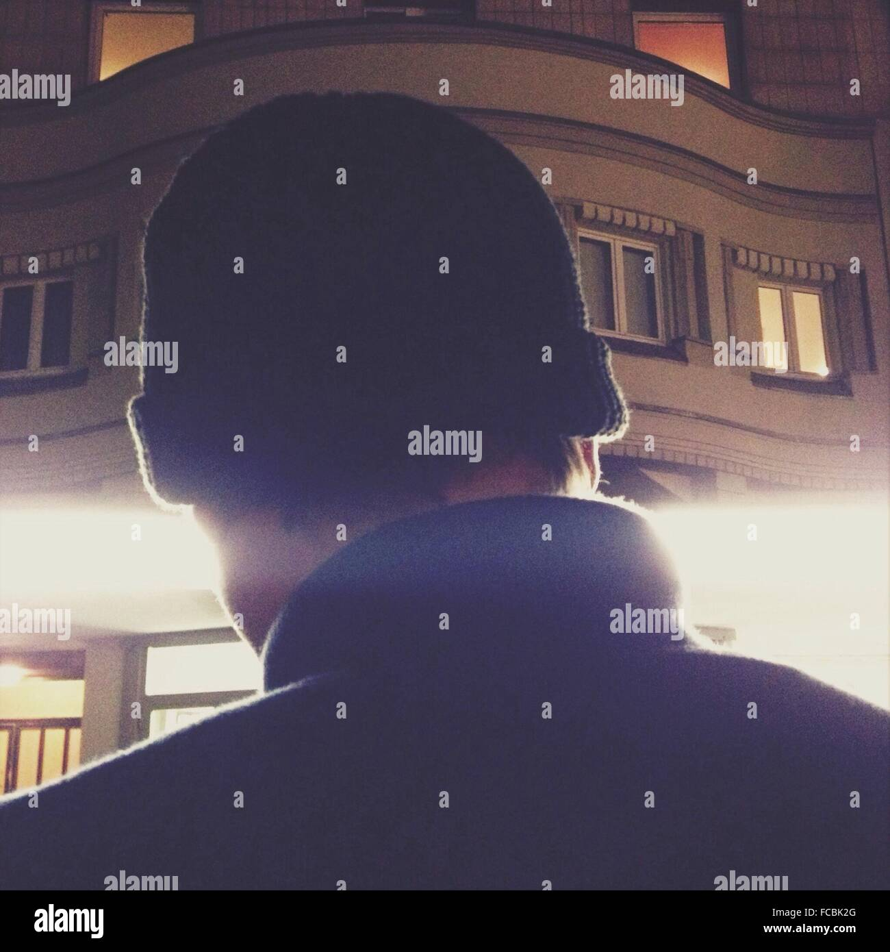 Rear View Of Man In Knit Hat Against Building - Stock Image