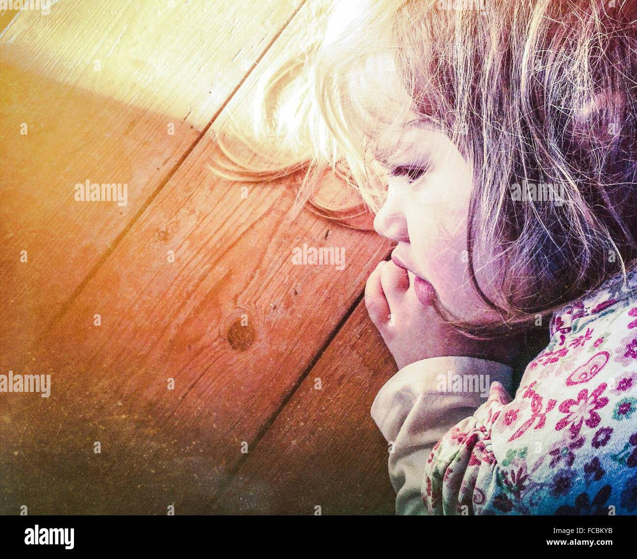 Close-Up Of Cute Young Girl Sleeping On Wooden Surface - Stock Image
