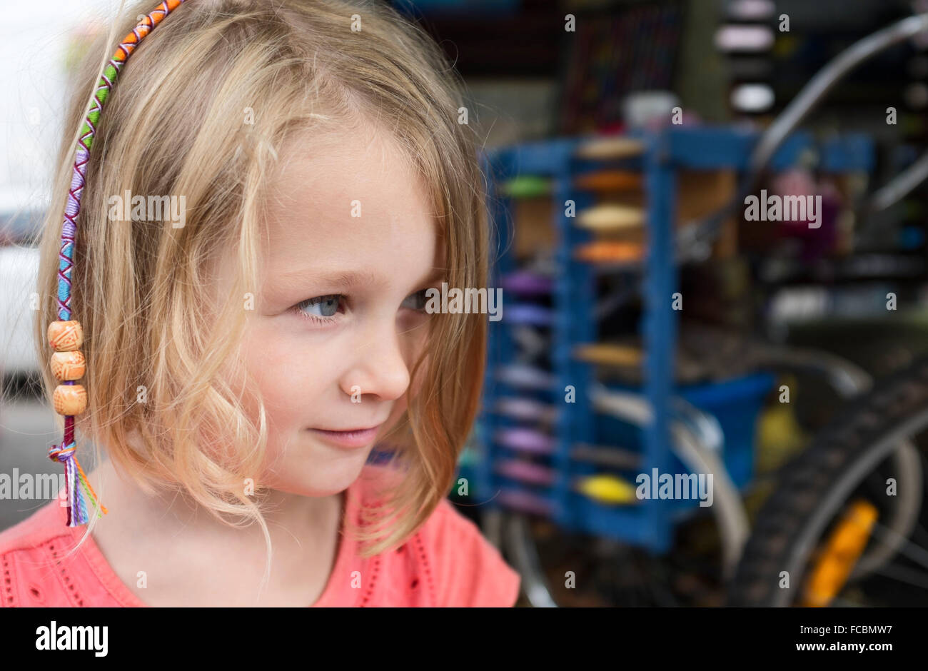 5 year old girl just had her hair braided with reals out of focus in background - Stock Image