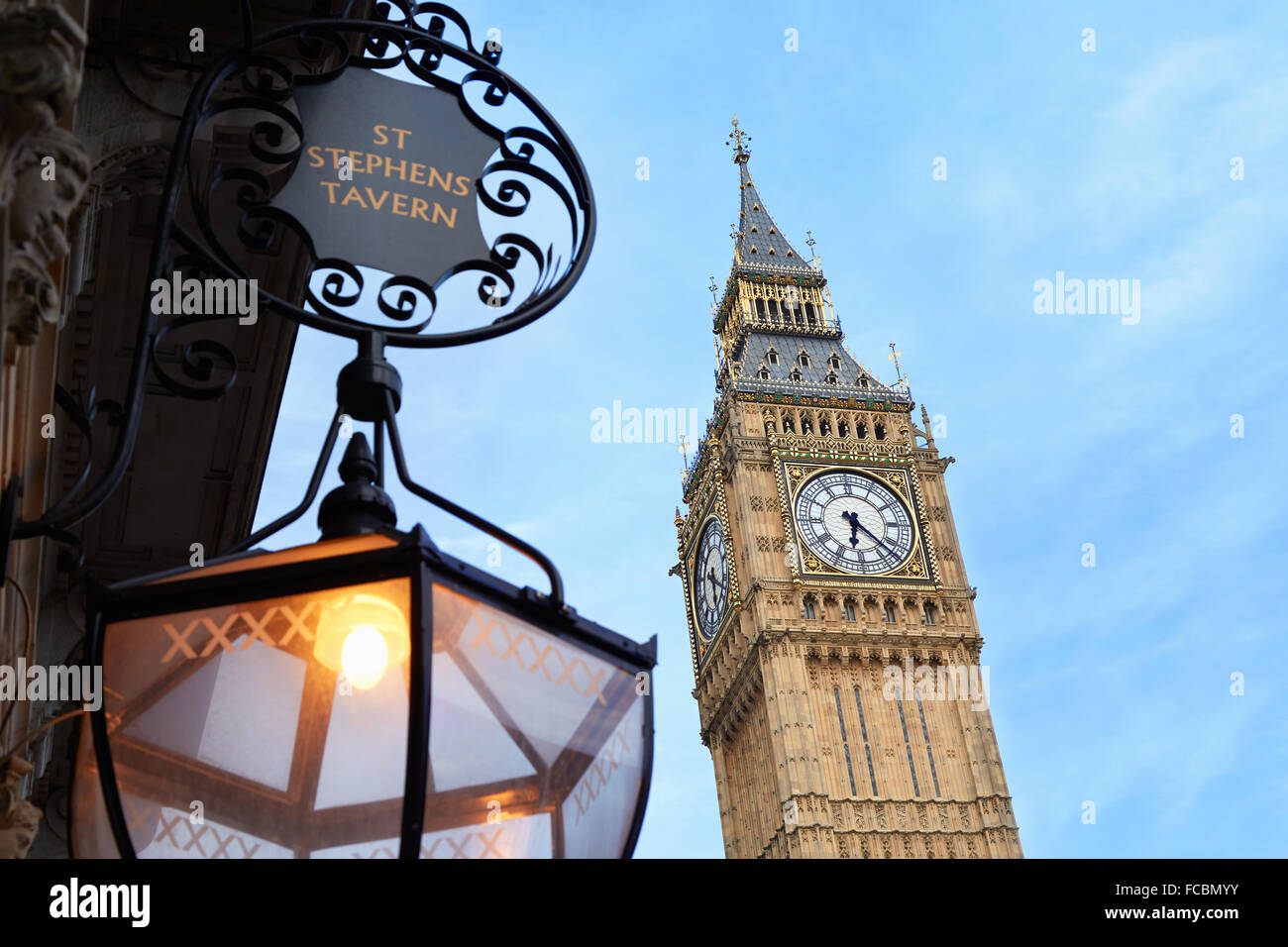 Big Ben and old St Stephens tavern lamp, blue sky in London - Stock Image