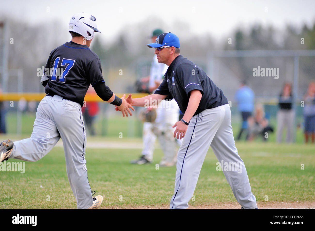 Third base coach congratulations a base runner as he rounds third base after hitting a home run in a high school - Stock Image