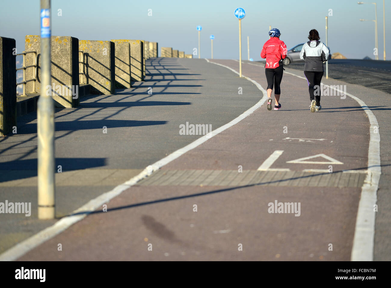 Joggers on Seaford seafront, UK - Stock Image