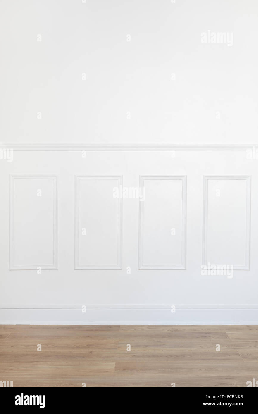Empty white room with parquet floor and wood trimmed wall - Stock Image