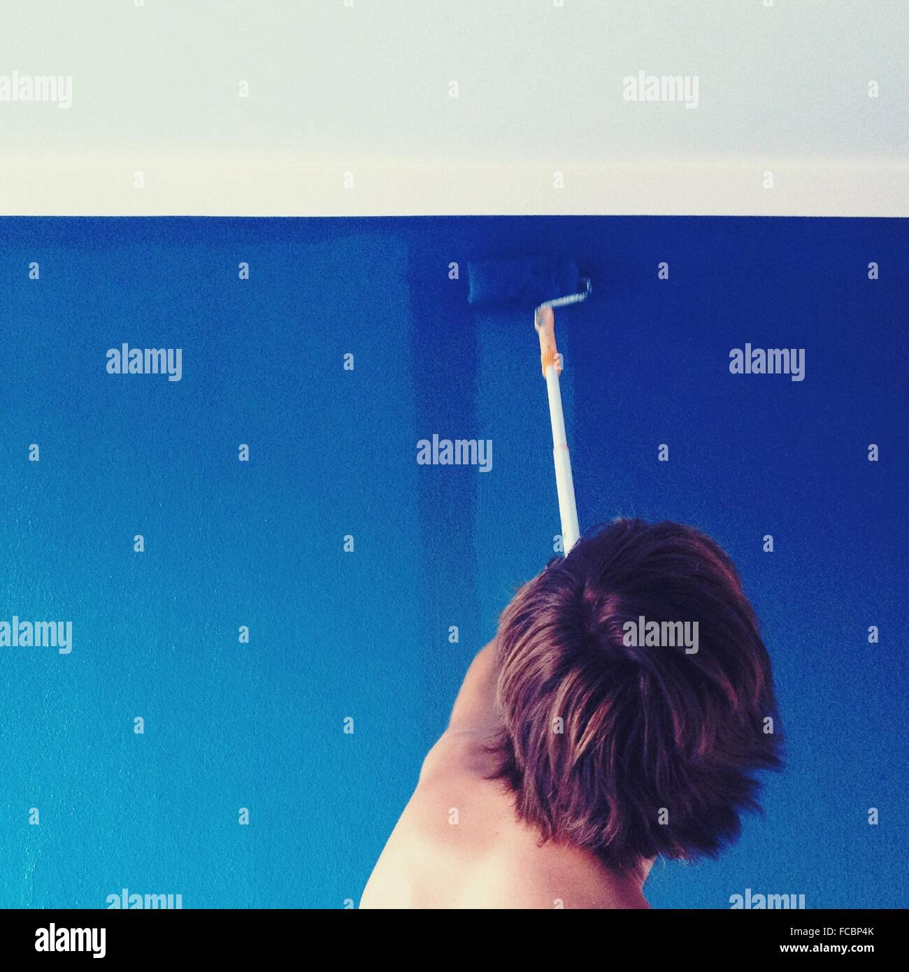 Rear View Of Man Painting Wall At Home - Stock Image