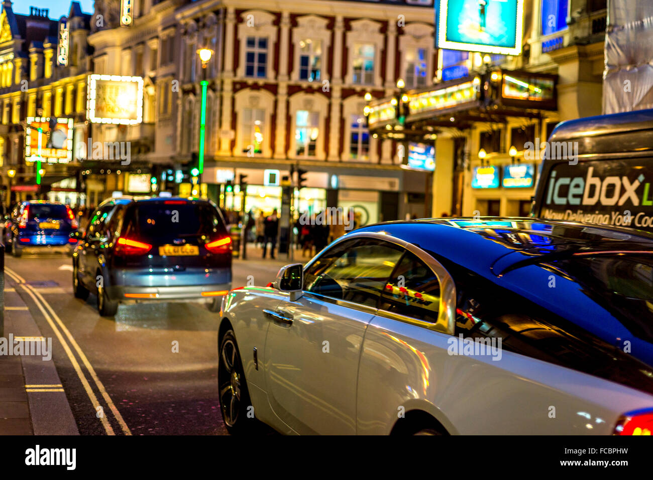 Busy London street with fantastic car in view - Stock Image