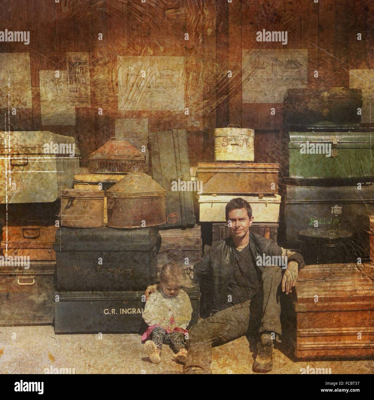 Portrait Of Father And Daughter Sitting Against Suitcases - Stock Image