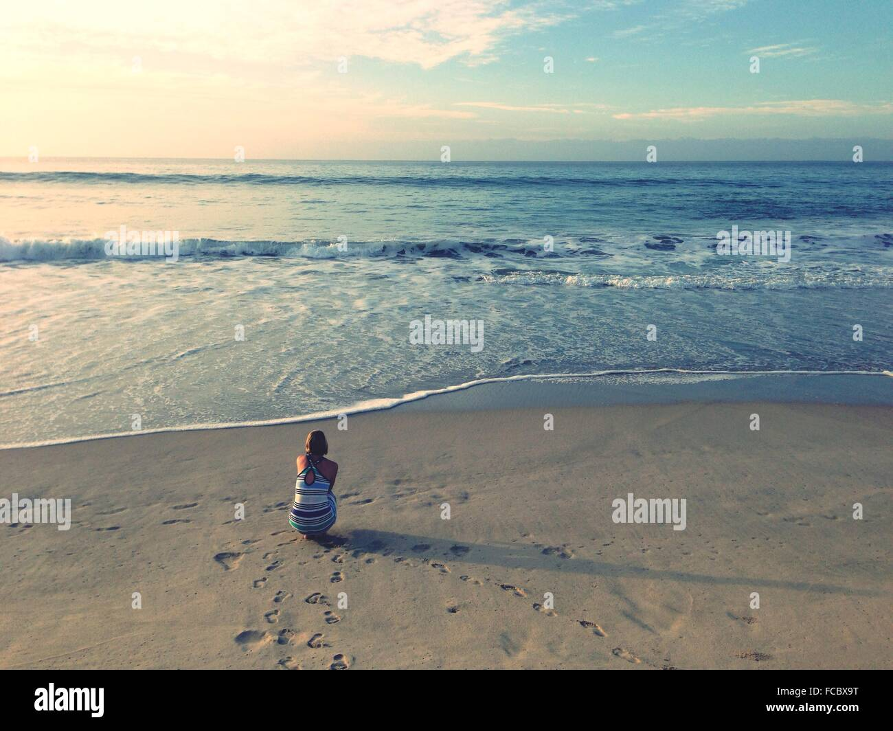 Woman Sitting On Sandy Beach - Stock Image