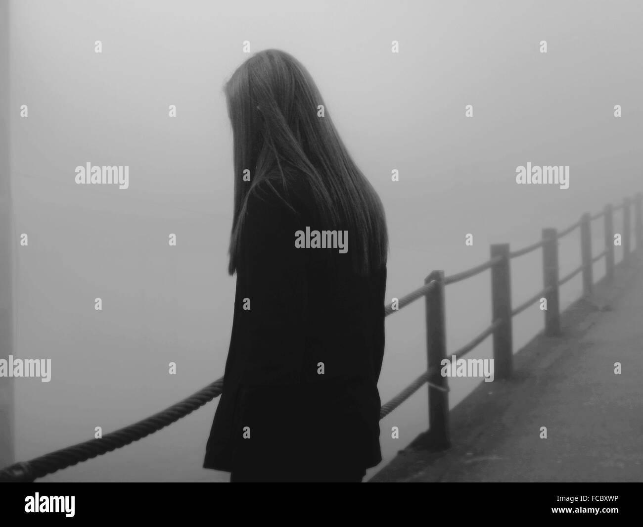 Rear View Of A Woman Looking Towards Clear Background - Stock Image