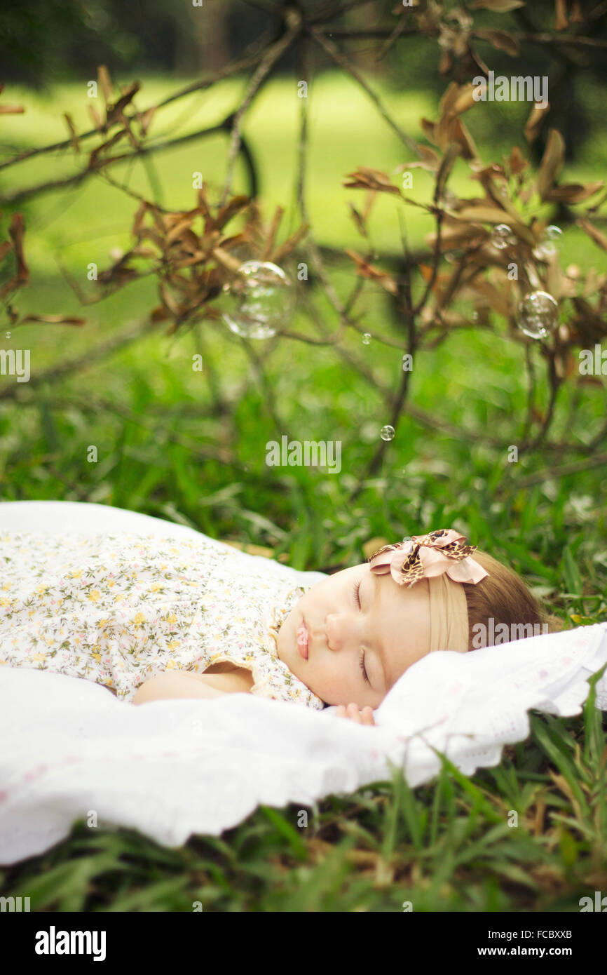Side View Of A Cute Baby Girl Sleeping On Grassland - Stock Image