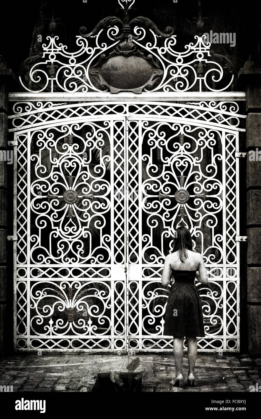 Rear View Of Woman Standing In Front Of Large Closed Gates - Stock Image