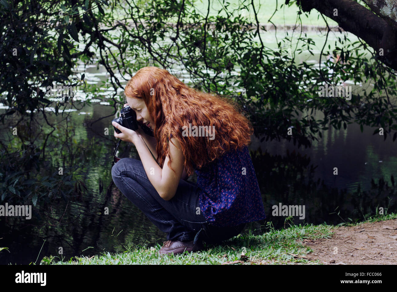Side View Of A Woman Photographing Plants - Stock Image
