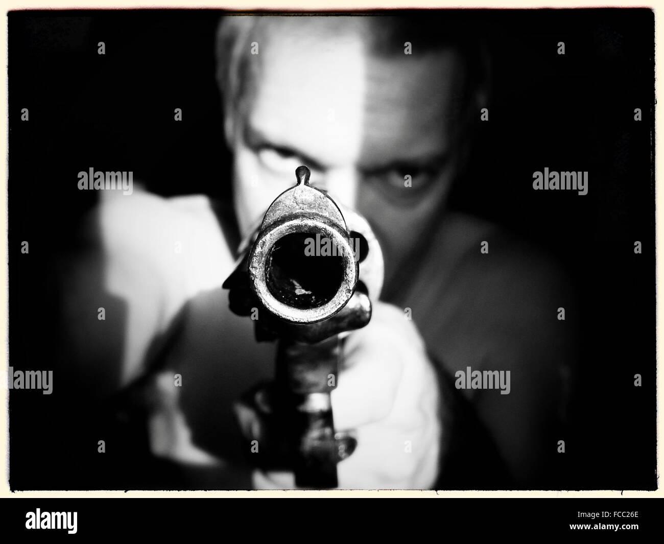 Man Aiming Gun At Camera - Stock Image