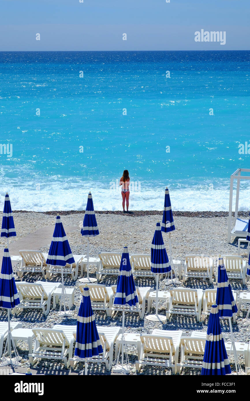 young girl woman beach umbrellas loungers holiday - Stock Image