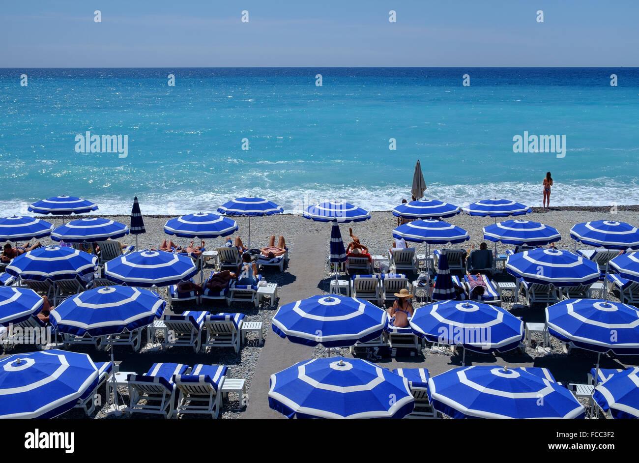 sunbathers beach umbrellas loungers holiday france - Stock Image