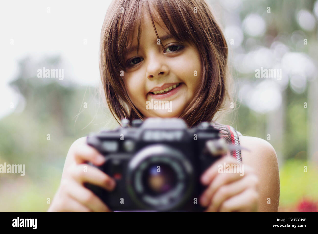 Portrait Of A Smiling Girl Holding Camera Outdoors - Stock Image