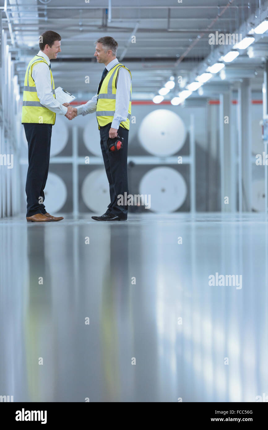 Businessmen in reflective clothing shaking hands in printing plant - Stock Image