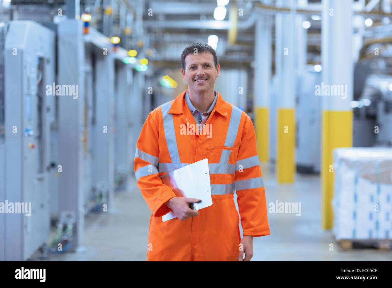 Portrait confident worker in reflective clothing with clipboard in factory - Stock Image