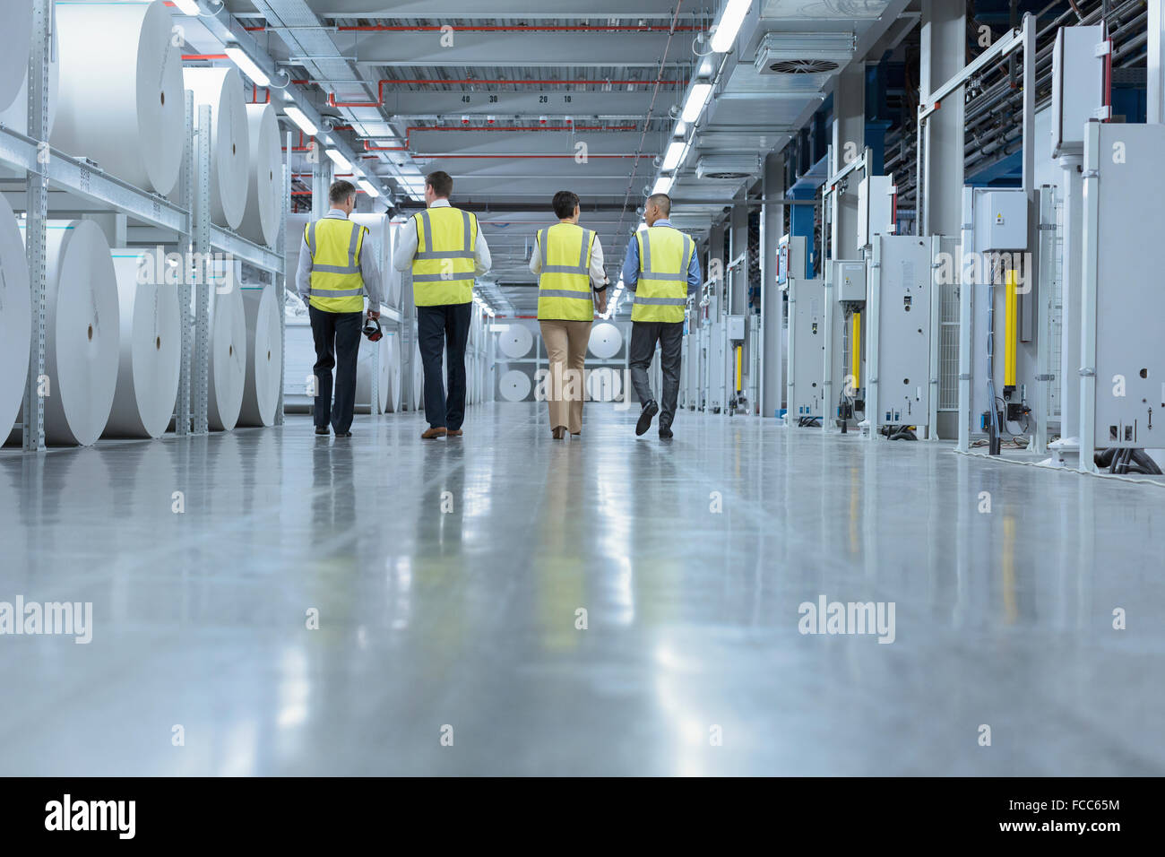 Workers in reflective clothing walking past large paper spools in printing plant - Stock Image
