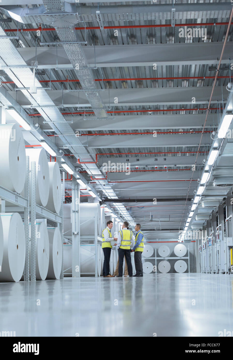 Workers in reflective clothing talking near large paper spools in printing plant - Stock Image