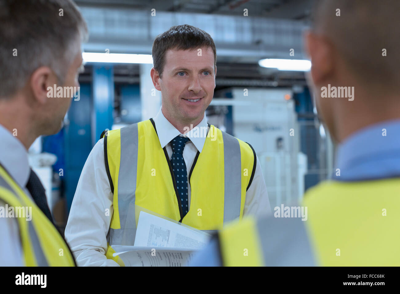 Workers in reflective clothing talking in factory - Stock Image