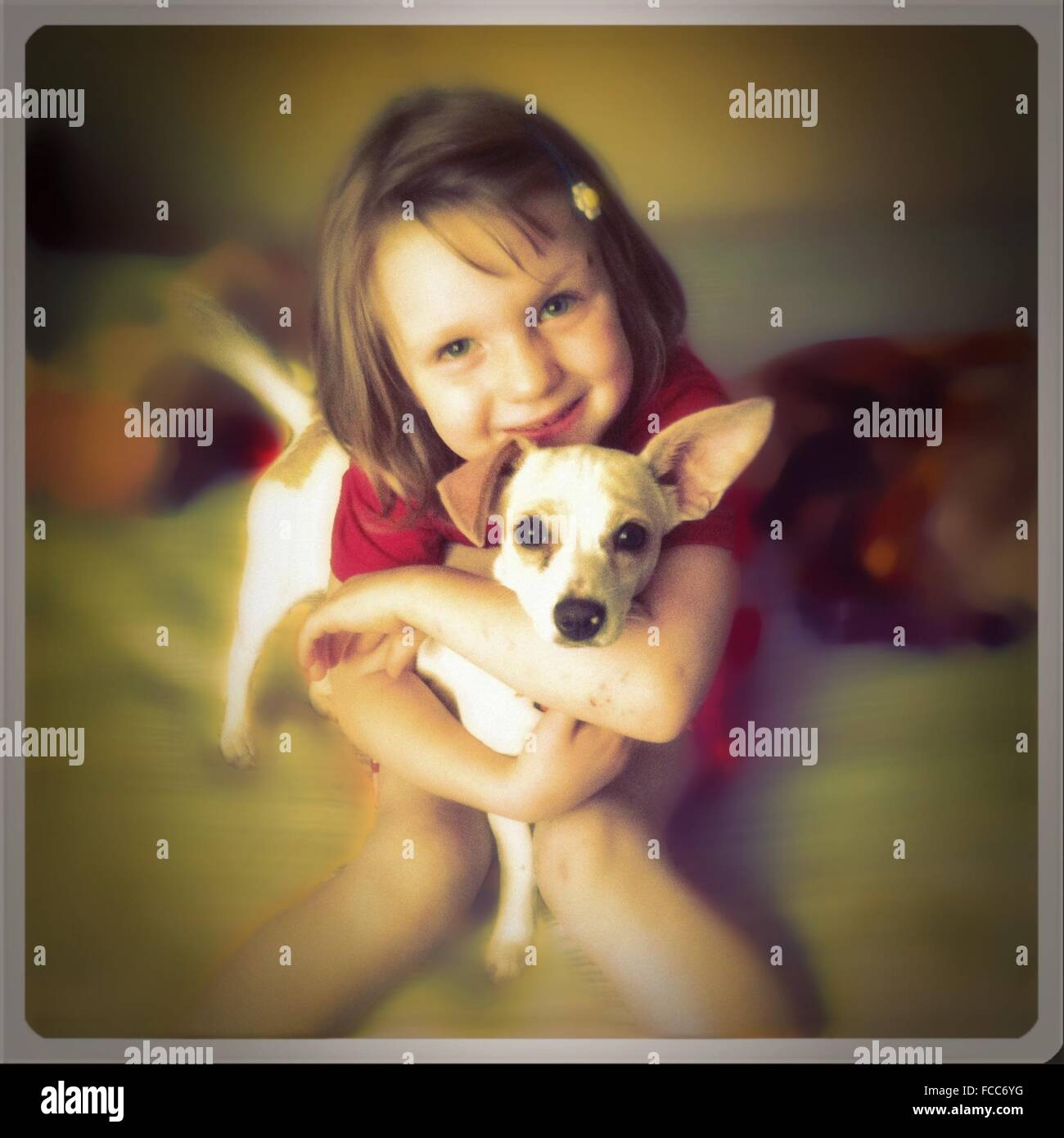 Young Girl Hugging Puppy - Stock Image